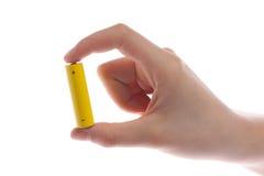die Hand des Mannes, die eine gelbe Batterie oder Batterie auf einem weißen Hintergrund lokalisiert hält Stockfotos