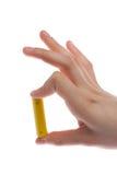 die Hand des Mannes, die eine gelbe Batterie oder Batterie auf einem weißen Hintergrund lokalisiert hält Lizenzfreies Stockfoto