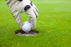Die Hand des Mannes, die einen Golfball in Loch auf setzt Lizenzfreie Stockfotografie