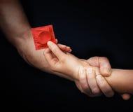 Die Hand des Mannes, die Frauenhand mit einem Kondom hält Lizenzfreies Stockbild