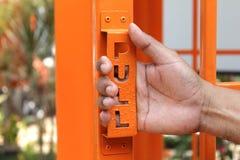 Die Hand des Mannes, die offene orange Tür von einem altmodischen Thailand zieht Stockbild