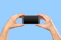 Die Hand des Mannes, die Smartphone hält Lizenzfreie Stockfotos