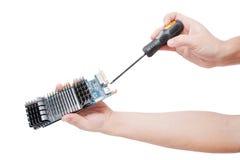 Die Hand des Mannes, die Videokarte mit Schraubendreher repariert. Stockbild