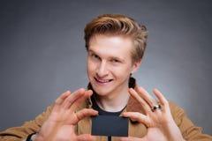 Die Hand des Mannes, die Visitenkarte zeigt Stockbild