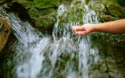 Die Hand des Mannes, die zu einem Wasserfrühling erreicht Stockbild