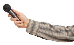 Die Hand des Mannes in einem grauen gestreiften Hemd, das ein Mikrofon hält Stockbilder