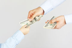 Die Hand des Mannes geben Geldamerikaner hundert Dollarscheine zur Jungenhand Lizenzfreie Stockfotos