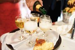Die Hand des Mannes gießt einen Champagner in Weingläser auf dem Behälter Lizenzfreies Stockbild