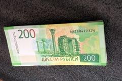 Die Hand des Mannes hält eine neue russische Banknote von zweihundert Rubeln vor dem hintergrund der Registrierkasse lizenzfreie stockbilder