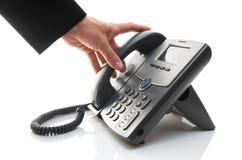 Die Hand des Mannes hebt das Telefon auf Stockfoto