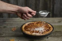 die Hand des Mannes mit dem Sieb, das Zuckerpulver über selbst gemachtem appl besprüht Stockbild