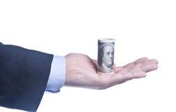Die Hand des Mannes mit einer Rolle von Dollar Lizenzfreie Stockfotos