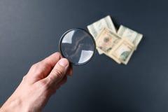 Die Hand des Mannes mit Lupe und Geld auf schwarzem Hintergrund Papierw?hrung Suchen nach Geld Konzept der Suche lizenzfreie stockfotografie