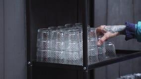 Die Hand des Mannes mit Tätowierung nimmt Paare von Gläsern vom schwarzen Fach heraus stock video