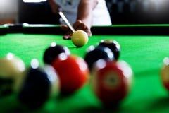 Die Hand des Mannes und Stichwortarm, der Snookerspiel spielt oder das Darauf abzielen vorbereitet, Poolbälle auf einem grünen Bi lizenzfreies stockfoto