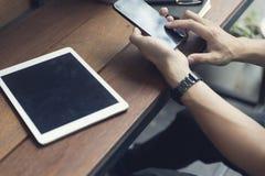 die Hand des Mannes unter Verwendung des Smartphone mit digitaler Tablette Stockbild