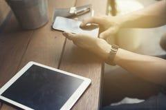 die Hand des Mannes unter Verwendung des Smartphone mit digitaler Tablette Lizenzfreie Stockfotos