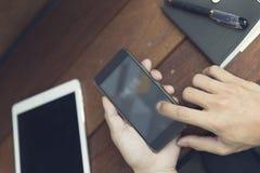 die Hand des Mannes unter Verwendung des Smartphone mit digitaler Tablette Lizenzfreies Stockfoto