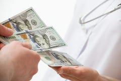 Die Hand des Patienten, die Doktor ein Geld gibt Lizenzfreies Stockfoto