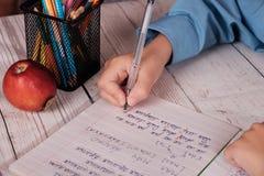 Die Hand des Schülers, der die Wörter und die Briefe in einem Notizbuch schreibt Lizenzfreies Stockbild