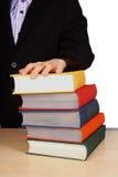 Die Hand des Schülers, die auf einem Stapel bunten Büchern liegt Lizenzfreie Stockfotos