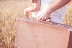Die Hand des Vaters, die einen Retro- Koffer und ein a hält Stockfotos