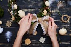 Die Hand, die Bogen auf einem handgemachten Ostern-Kranz bindet, Ebene legen Zusammensetzung stockbild