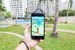 Die Hand, die ein Mobiltelefon spielt Pokemon hält, gehen stockfotos
