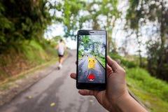 Die Hand, die ein Mobiltelefon spielt Pokemon hält, gehen lizenzfreie stockbilder