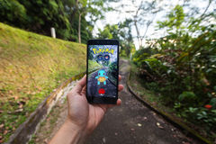 Die Hand, die ein Mobiltelefon spielt Pokemon hält, gehen Stockfotografie