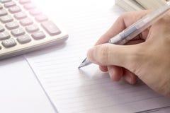 Die Hand, die einen Stift hält, schreiben für etwas Lizenzfreies Stockbild