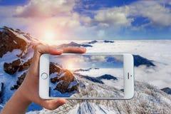 Die Hand, die intelligentes Telefon hält, machen ein Foto an Deogyusan-Bergen Stockfotos
