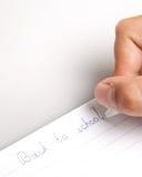 Die Hand, die zu den Schreibenbüchern schreibt. Lizenzfreies Stockfoto