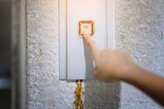 Die Hand drückt auf den alten Aufzugsknopf, roter Knopf abschluß Stockbilder