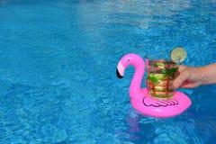 Die Hand, die ein Getränk in einem aufblasbaren rosa Flamingo hält, trinkt Halter im Swimmingpool stockfotos