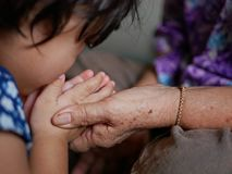 Die Hand einer älteren Person, welche die Hände eines kleinen Babys während das Baby tut das wai, Respekt zu den Ältesten zah stockfotografie