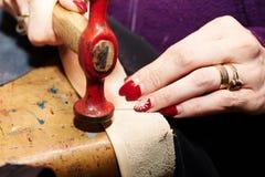 Die Hand einer Frau, die einen Streifen des Leders mit einem Hammer funktioniert stockfoto