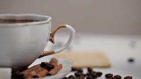 Die Hand einer Frau nimmt eine Tasse Kaffee-Nahaufnahme Kaffeebohnen und Zimt stock video footage