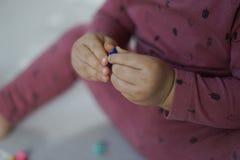 Die Hand eines Babys, die ein kleines Spielzeug mit beiden Händen berührt stockfotografie