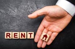 Die Hand eines Geschäftsmannes in einem Anzug hält einen Würfel auf der Palme mit einem Bild des Hauses zur Wortmiete Stockfoto