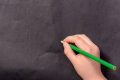 Die Hand eines kleinen Jungen schreibt einen Bleistift auf einen schwarzen Hintergrund Stockfotos