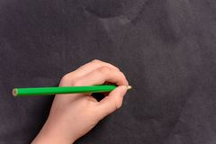 Die Hand eines kleinen Jungen schreibt einen Bleistift auf einen schwarzen Hintergrund Stockbilder