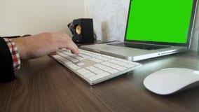Die Hand eines Mannes, die auf einem Tastatur-PC Grünschirm schreibt stock footage