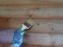 Die Hand eines Mannes mit einer B?rste, zum einer h?lzernen Wand zu malen stockfotografie