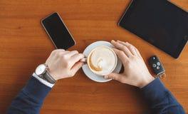 Die Hand eines Mannes, Schlüssel eines Tasse Kaffees, der Tablette und des Autos Lizenzfreie Stockfotos