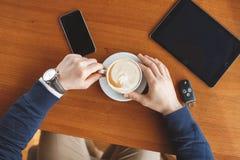 Die Hand eines Mannes, Schlüssel eines Tasse Kaffees, der Tablette und des Autos Lizenzfreie Stockfotografie