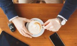 Die Hand eines Mannes, Schlüssel eines Tasse Kaffees, der Tablette und des Autos Stockbild