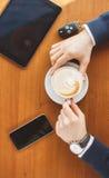 Die Hand eines Mannes, Schlüssel eines Tasse Kaffees, der Tablette und des Autos Stockfotografie