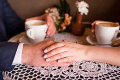 Die Hand eines Mannes und der Frau Zwei Schalen mit Cappuccino Romantisches Abendessen, ein Datum Stockfotografie