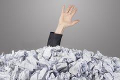 Die Hand erreicht heraus vom großen Haufen der zerknitterten Papiere Lizenzfreie Stockfotos